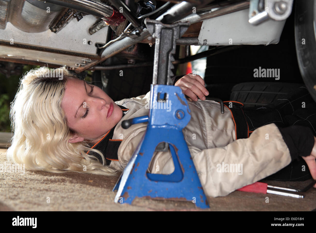 Donna che fissa il suo midget race car Immagini Stock