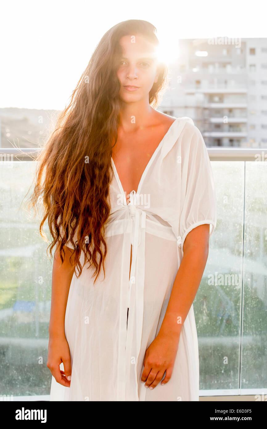 Giovane donna fiducioso nel suo 20s con capelli lunghi marrone in casual abito bianco. Retroilluminati da sun. Modello Immagini Stock
