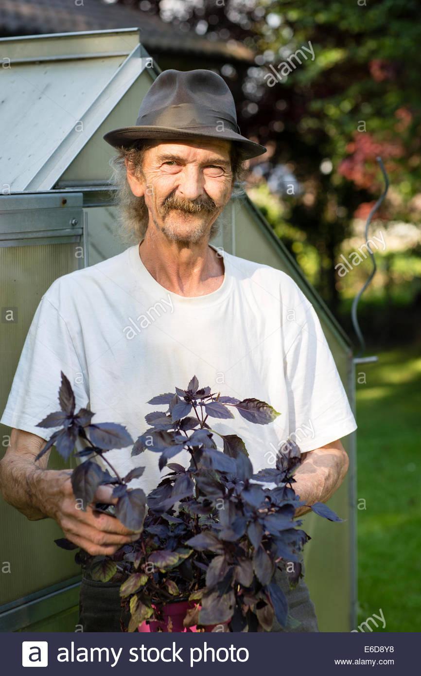 Ritratto di uomo anziano con il cappello e i baffi in piedi di fronte ad una  serra 7c9a255d7a7a