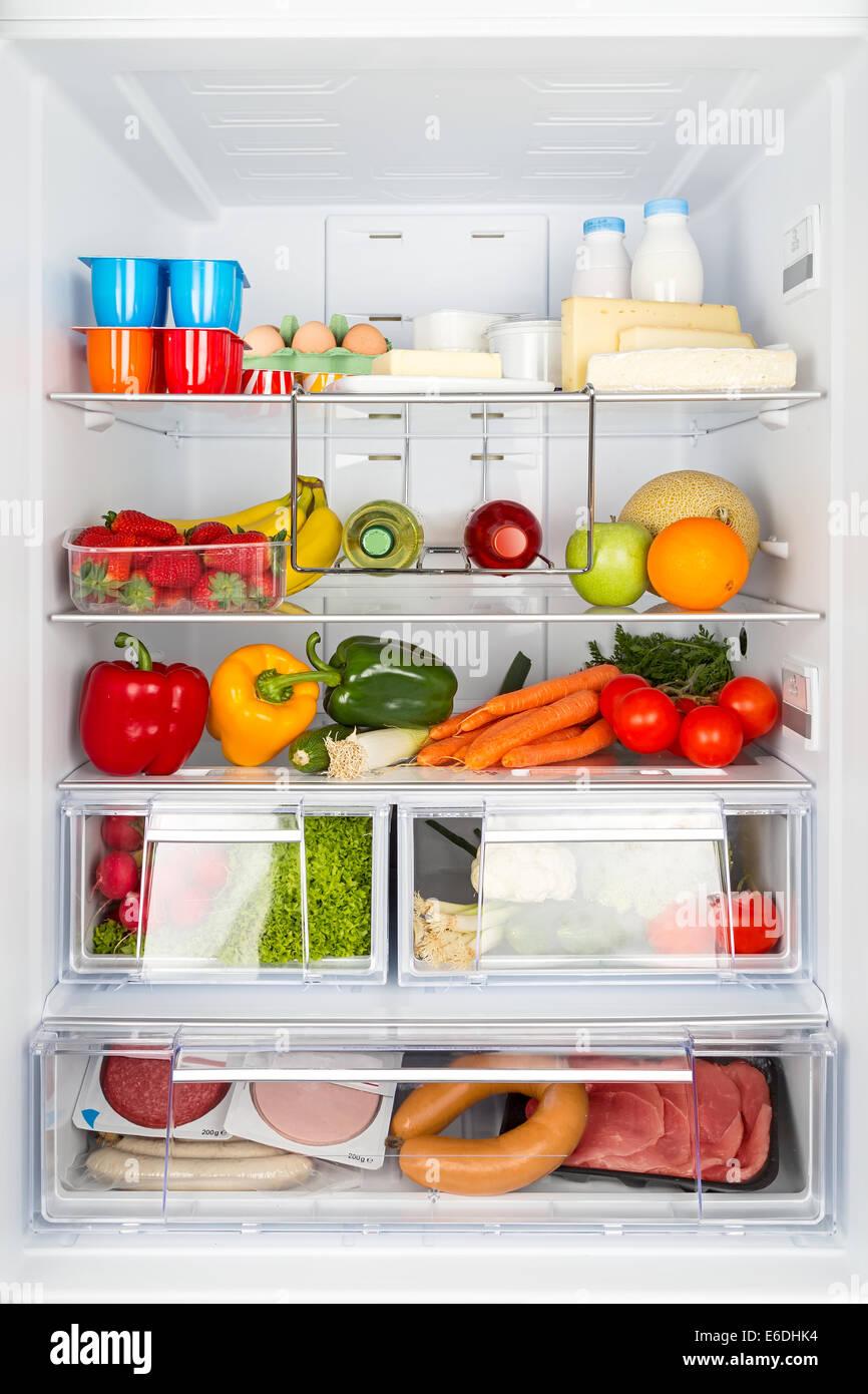 Aprire refrigeratored riempito con i prodotti alimentari Immagini Stock