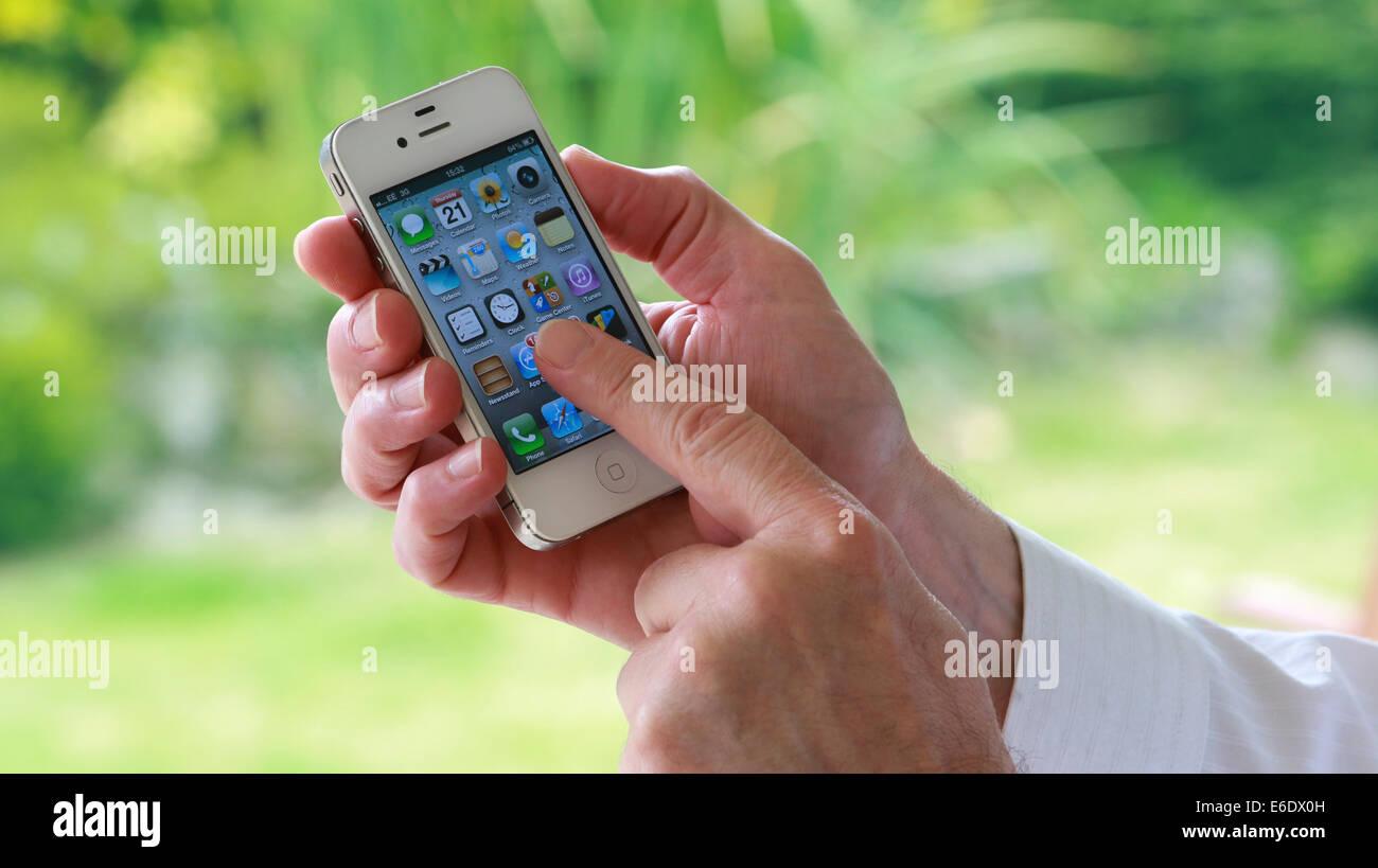 Una mano d'uomo in possesso di un i-phone premendo un app sullo schermo. Immagini Stock