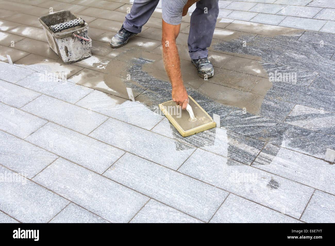 Lavoratore riempitivi di fughe di piastrelle con frattazzo in
