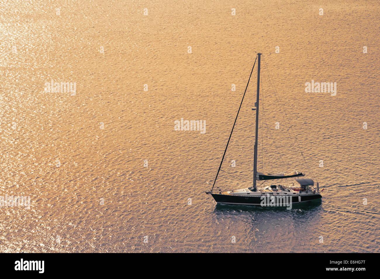 Barca a vela sul mare con tramonto per un concetto dello sfondo. Immagini Stock