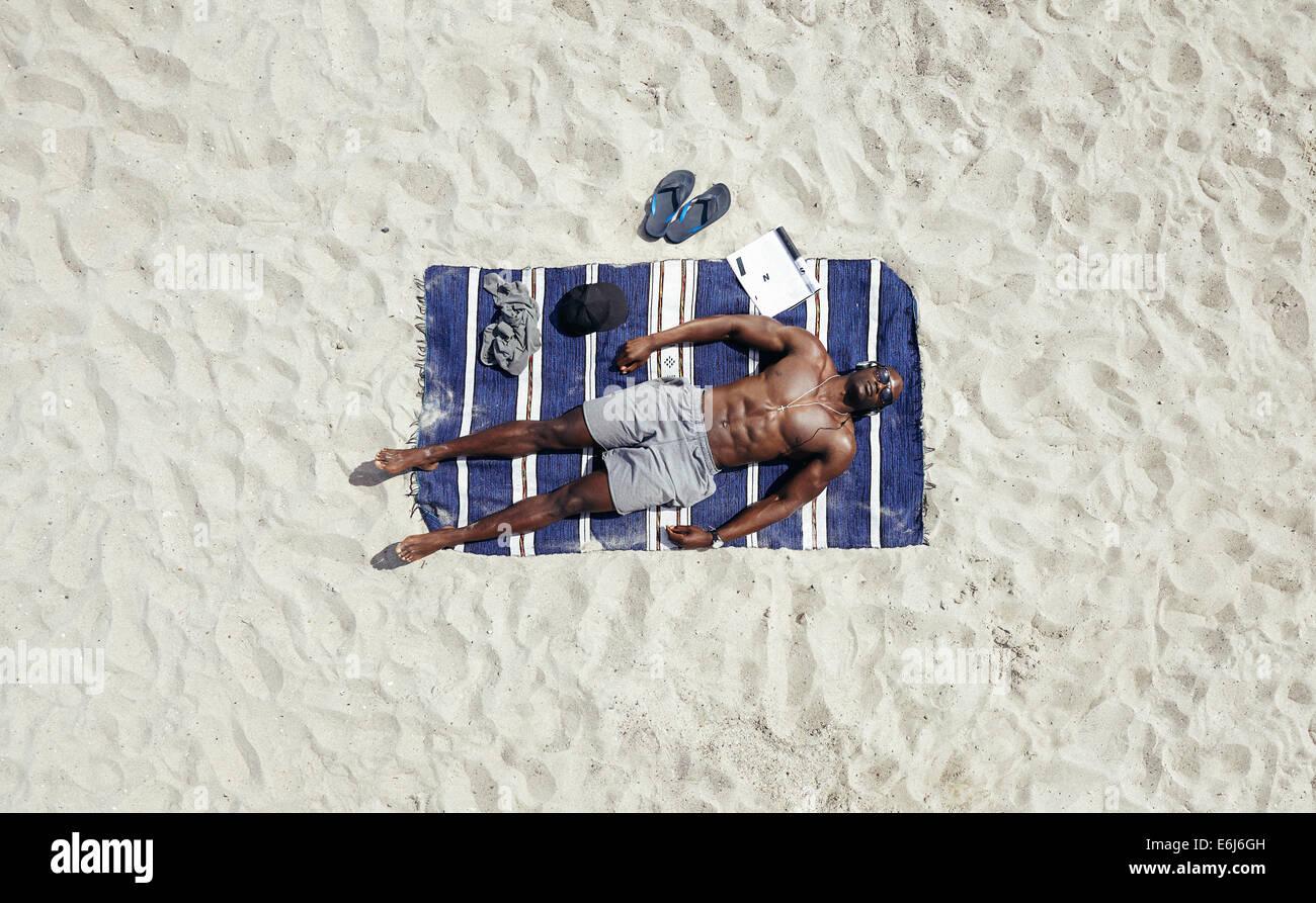 Vista superiore del giovane uomo disteso shirtless su una spiaggia mat. African modello maschile a prendere il sole. Immagini Stock