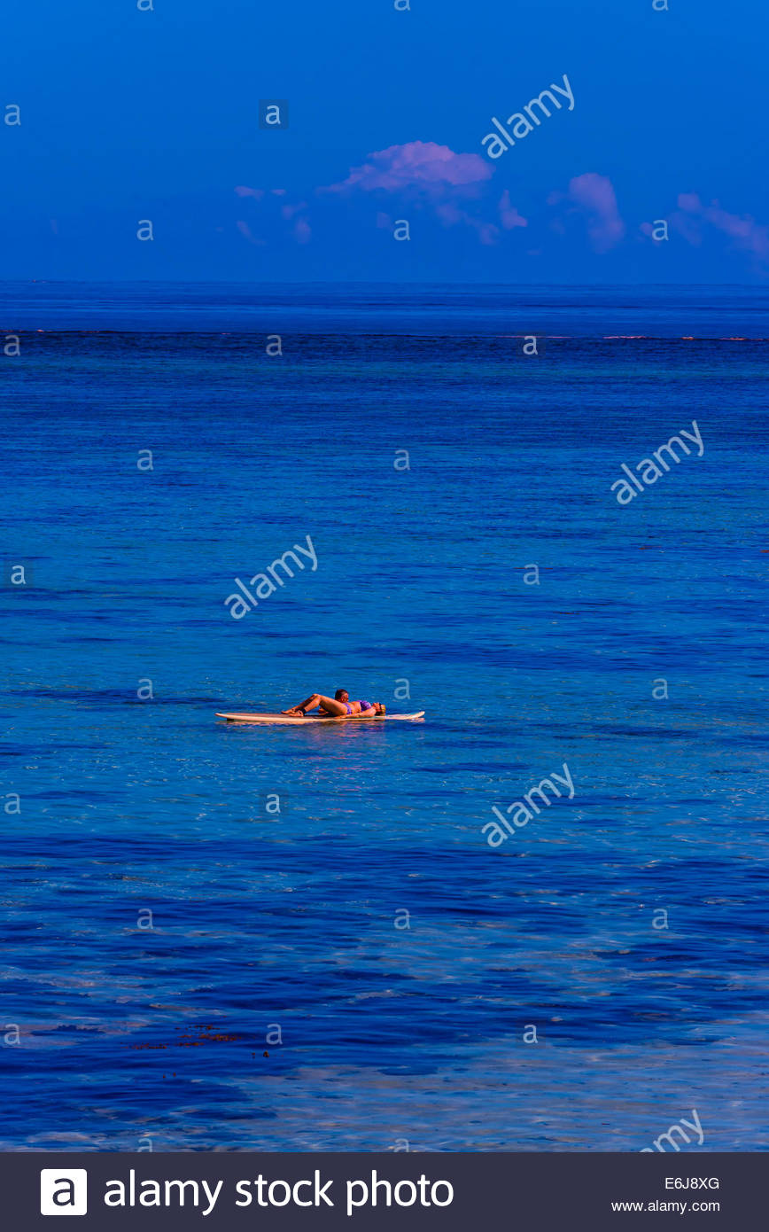 Giovane sdraiati su un paddleboard, Hilton Moorea Lagoon Resort, l'isola di Moorea, Polinesia francese. Immagini Stock