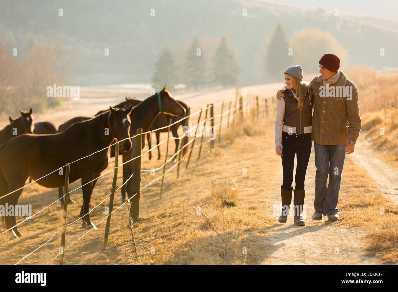 Giovani coppie romantiche passeggiate a cavallo fattoria Immagini Stock