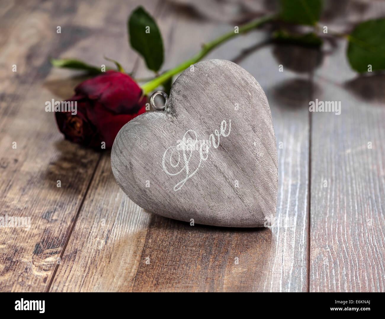 Il giorno di San Valentino il simbolo. Cuore su uno sfondo di legno con una rosa rossa. Immagini Stock