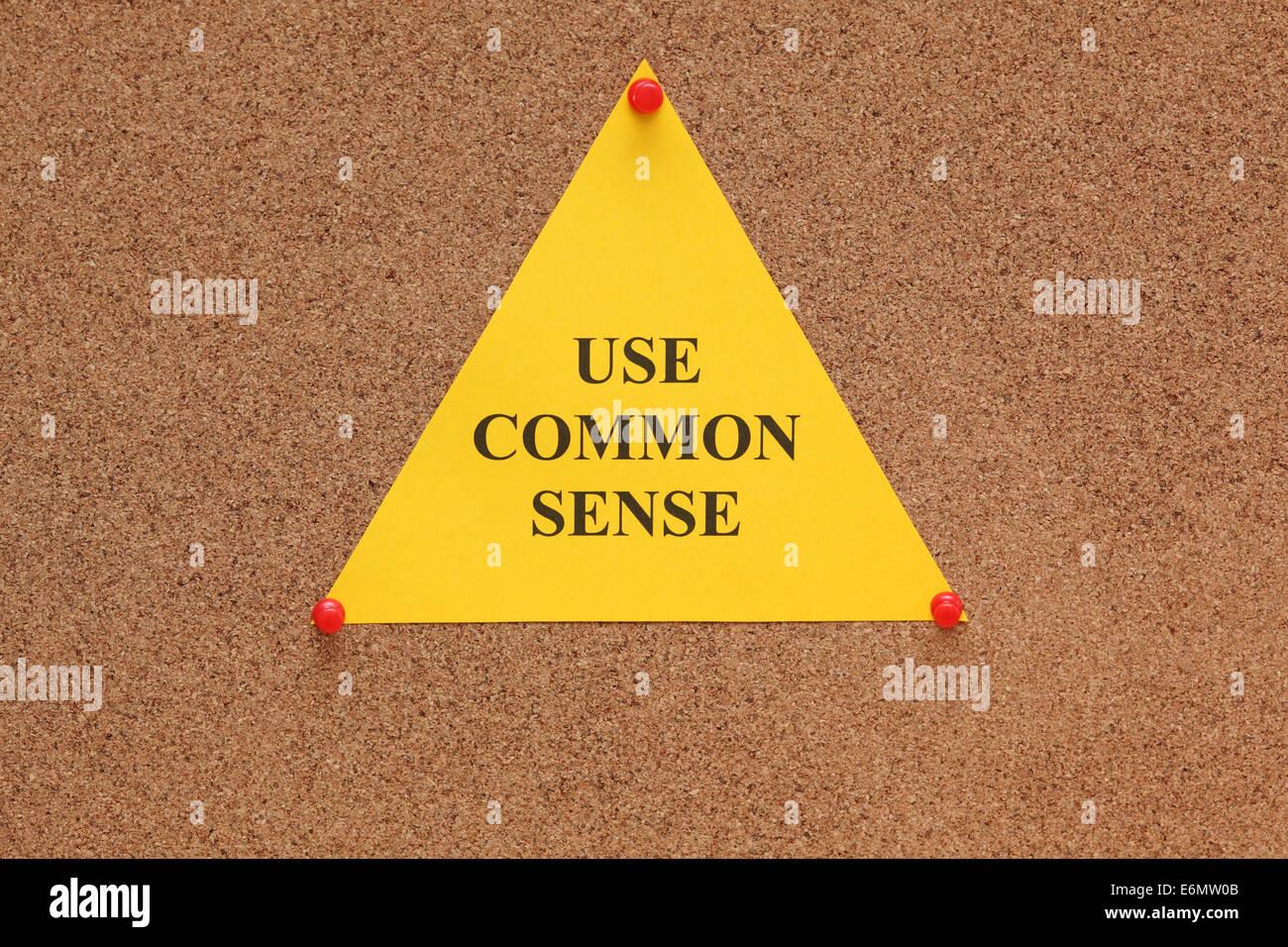 """Carta triangolare nota con le parole 'usare il buon senso"""" sulla bacheca di sughero (bulletin board). Immagini Stock"""