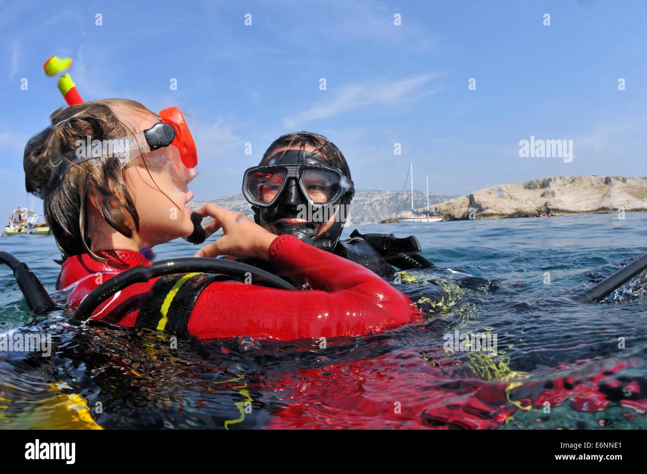La ragazza (di età compresa tra i 9) con il suo istruttore di immersioni torna dal subacqueo, Mare mediterraneo, Foto Stock
