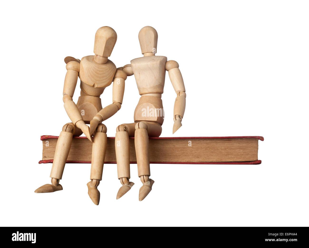 Il conforto di un amico rappresentato da due figurine su un Libro isolato su sfondo bianco Immagini Stock