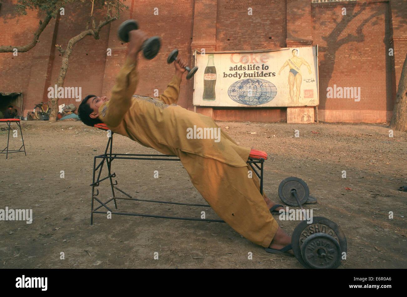 Giovane uomo che fa i pesi in un club sportivo. Sullo sfondo una pubblicità per la coca cola. L'uomo è Immagini Stock