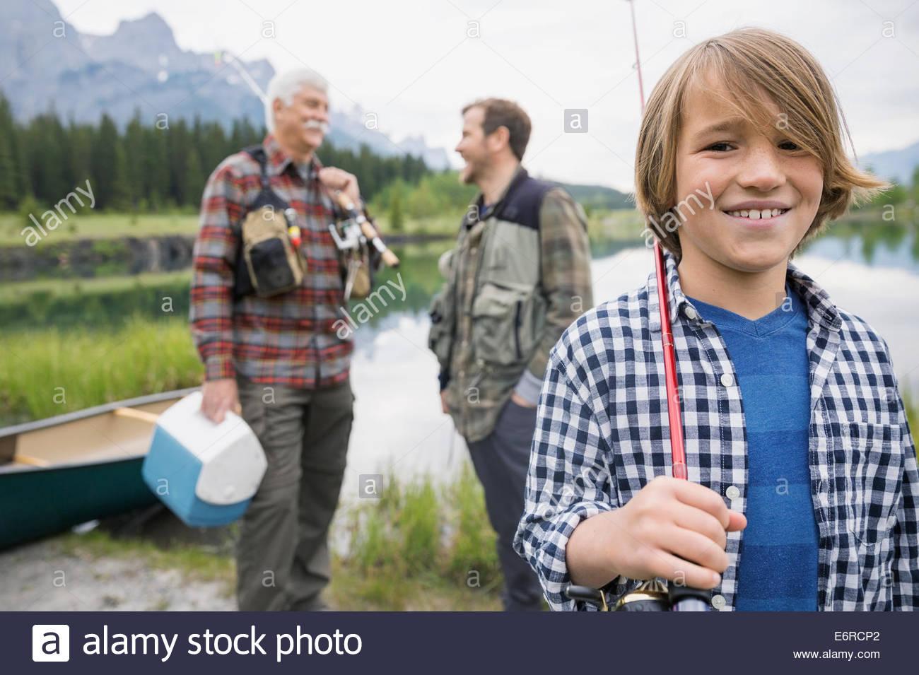 Tre generazioni di uomini in piedi dal lago ancora Immagini Stock