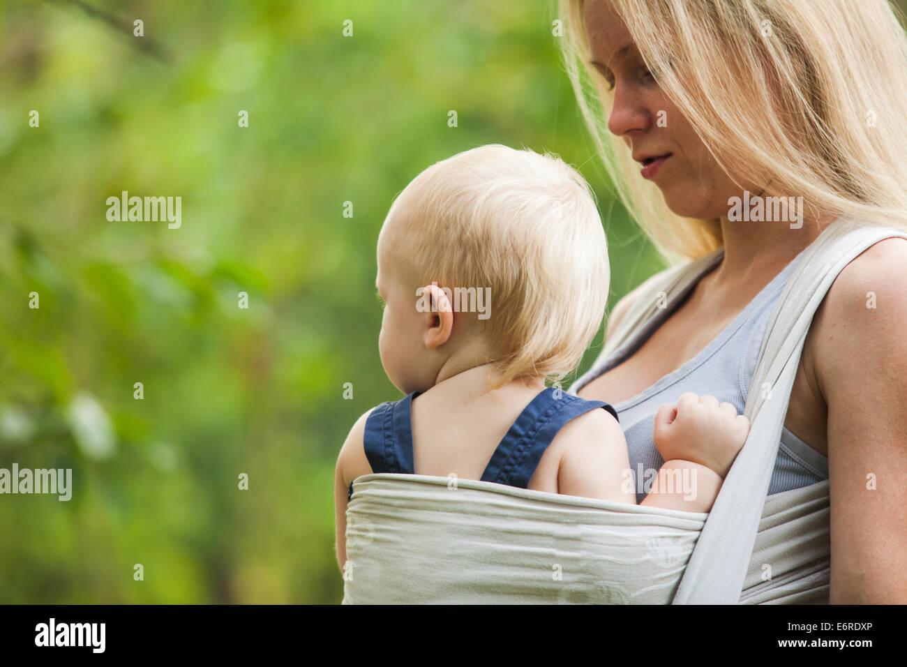 La madre sta portando il suo bambino e a piedi. Nella Baby Sling all'aperto. Immagini Stock