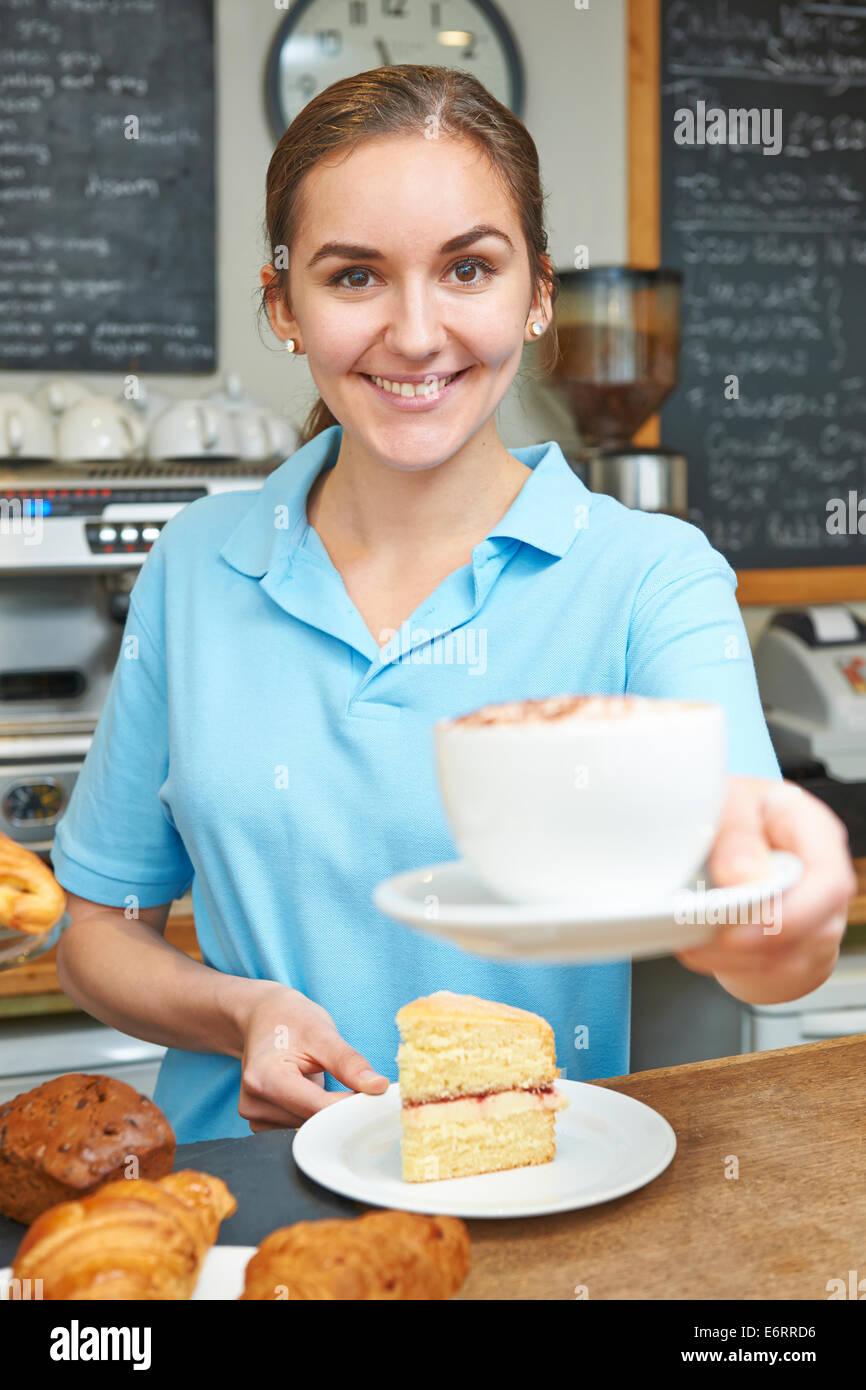 Cameriera In Cafe che serve il cliente con caffè Immagini Stock