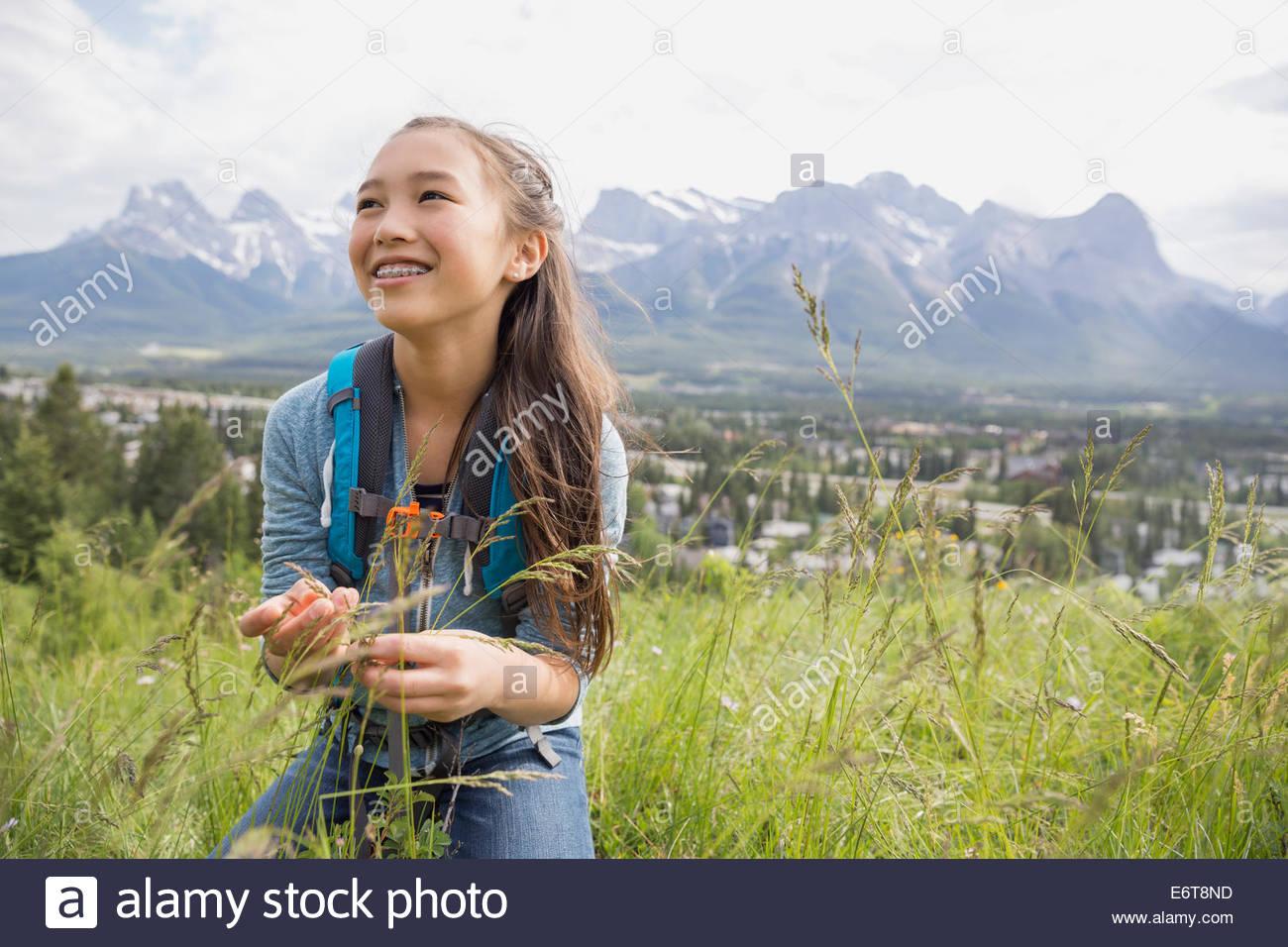 Ragazza esaminando le piante sulla collina rurale Immagini Stock