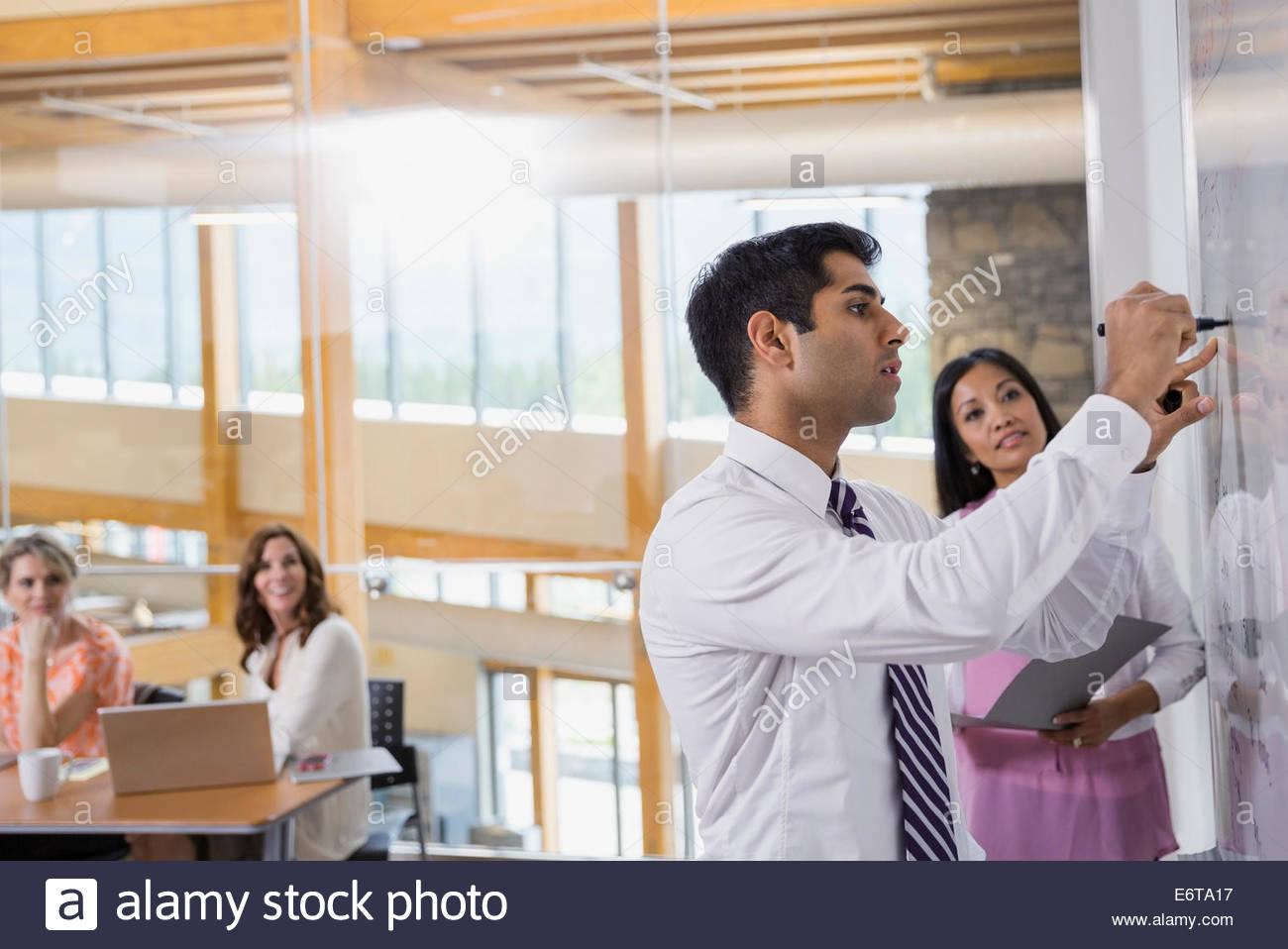 Imprenditore iscritto sul pannello bianco in riunione Immagini Stock
