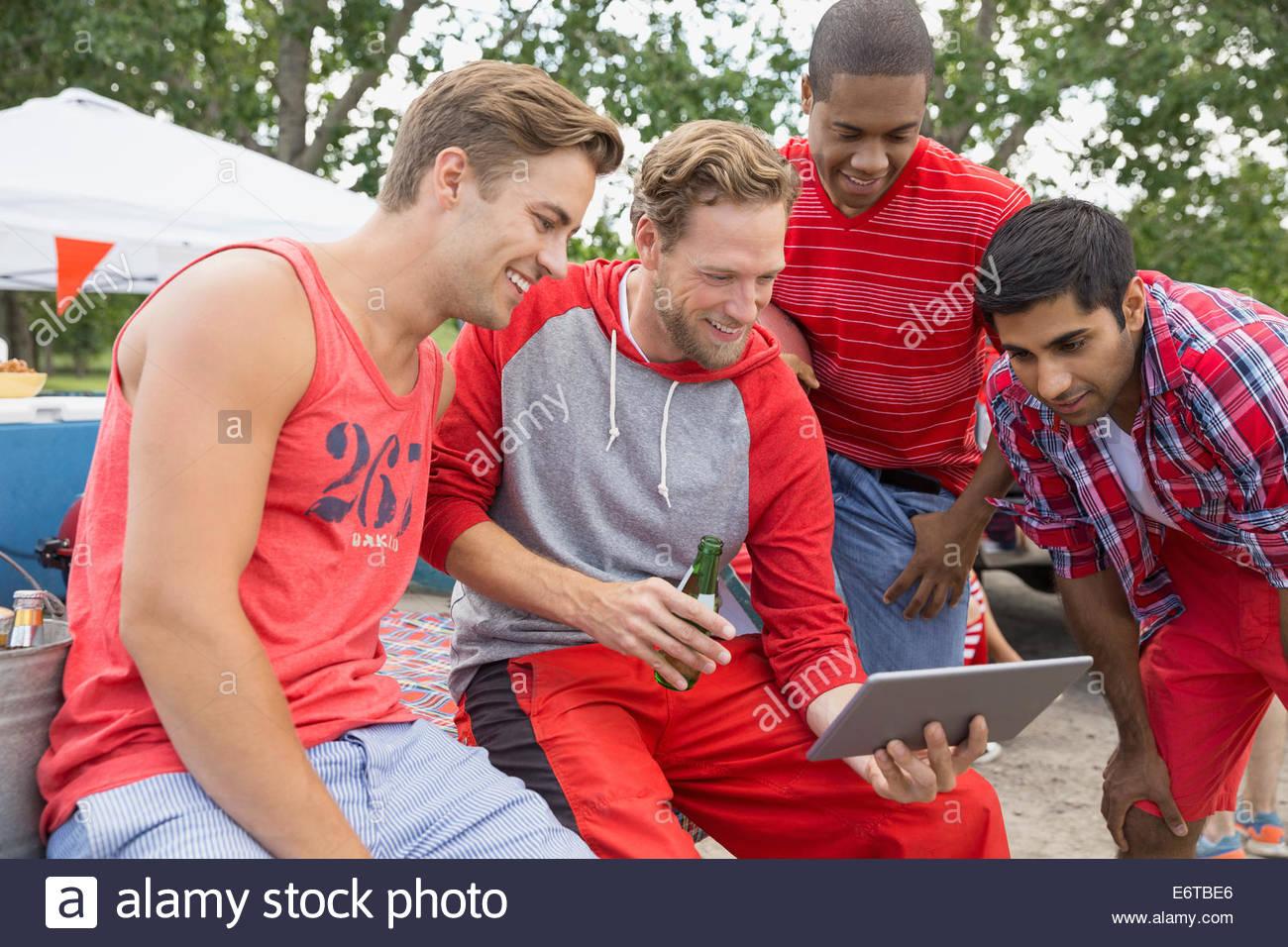Gli uomini con tavoletta digitale al barbecue del portellone Immagini Stock