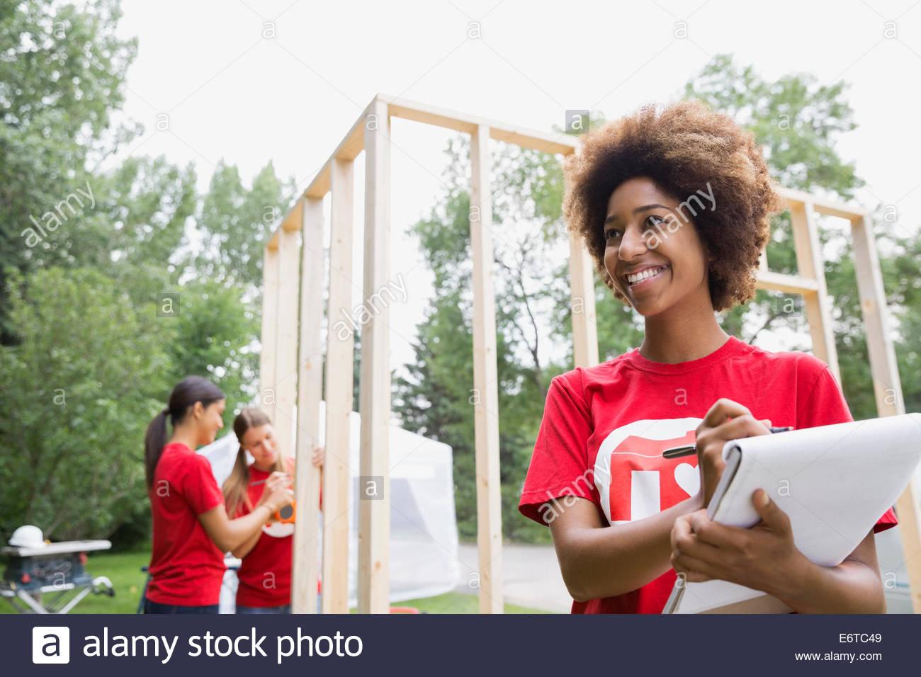 Volontario con notepad vicino al telaio di costruzione Immagini Stock