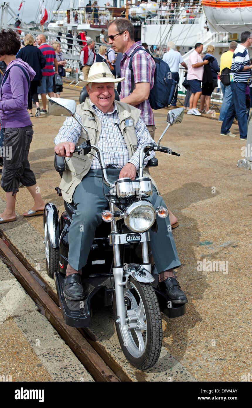 Un senior disabili gentleman sulla sua mobilità del veicolo di trasporto Immagini Stock