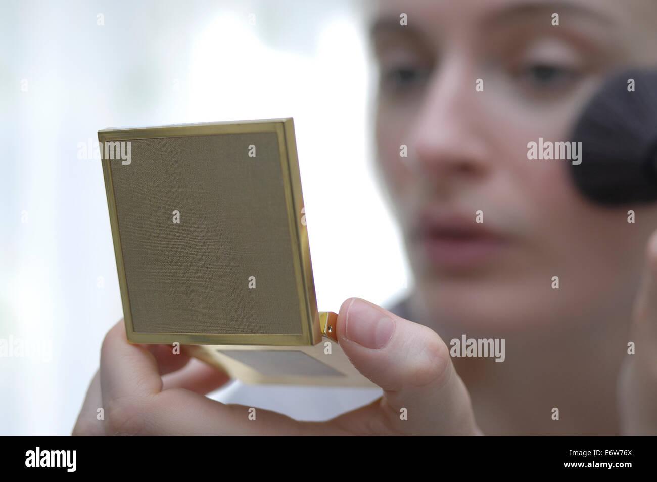 Donna che guarda nello specchio di mano mentre utilizzando la spazzola per il trucco Immagini Stock