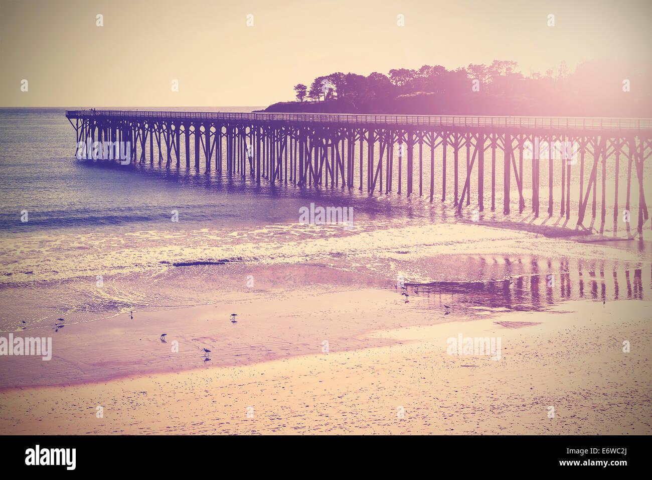 Vintage ponte di legno in spiaggia al tramonto, California, USA. Immagini Stock