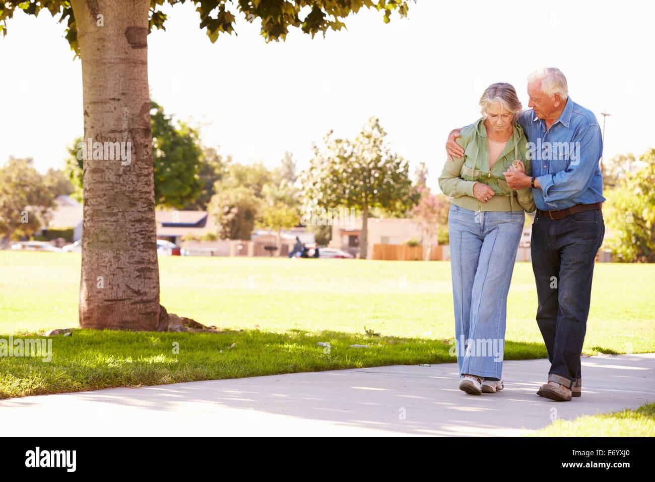 Senior uomo aiutando moglie come essi passeggiata nel parco insieme Immagini Stock
