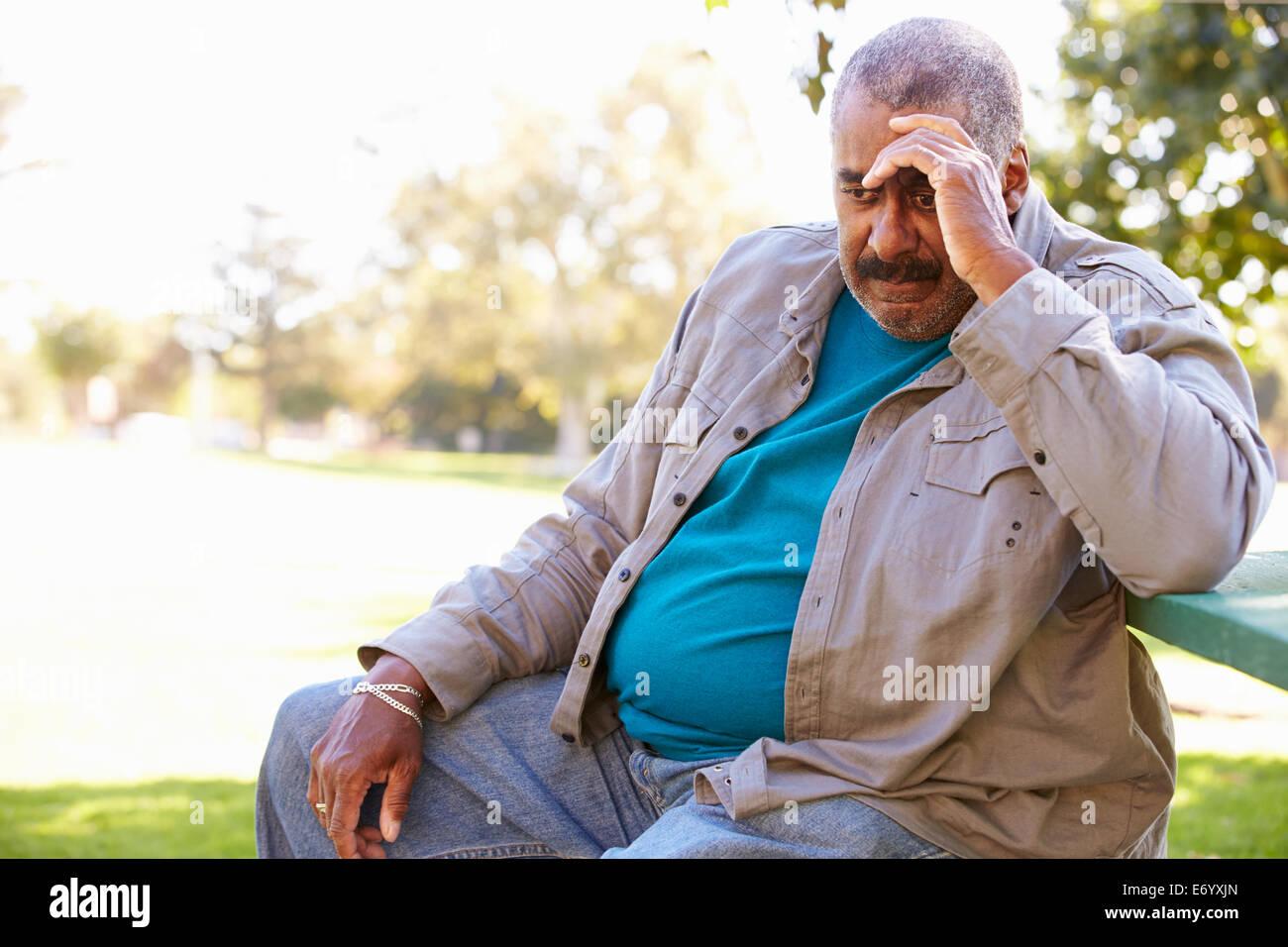 Premuto Senior uomo seduto al di fuori Immagini Stock