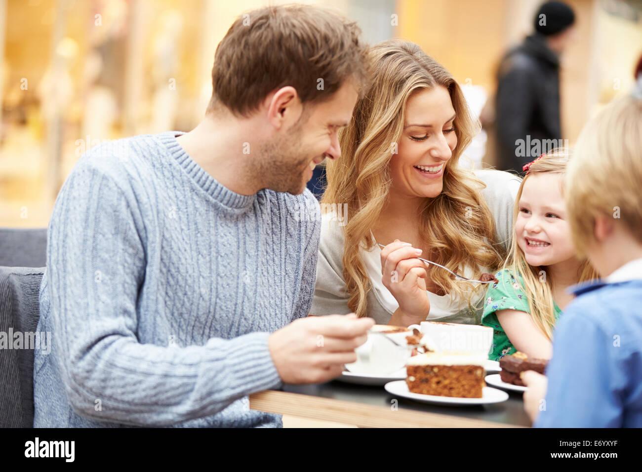 Famiglia gustando uno spuntino nella caffetteria insieme Immagini Stock