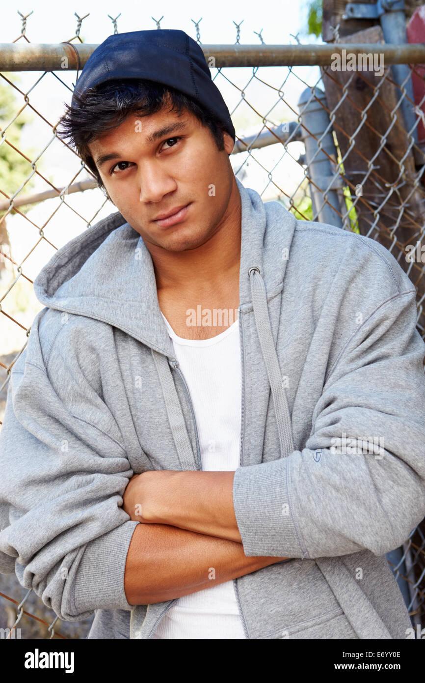 Ritratto di giovane uomo nel contesto urbano in piedi da recinzione Immagini Stock