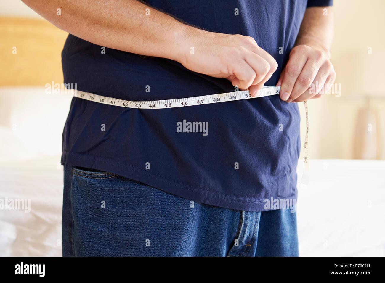 Close Up di sovrappeso uomo cintura di misurazione Immagini Stock