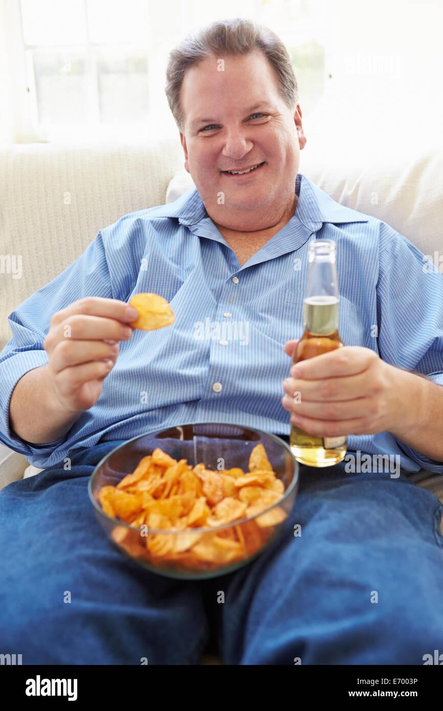 Uomo sovrappeso a casa a mangiare patatine e bere birra Immagini Stock