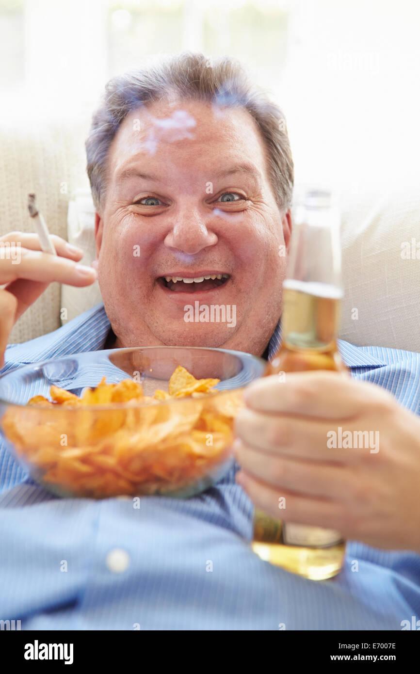 Il sovrappeso uomo mangiare patatine, bere birra e fumare Immagini Stock
