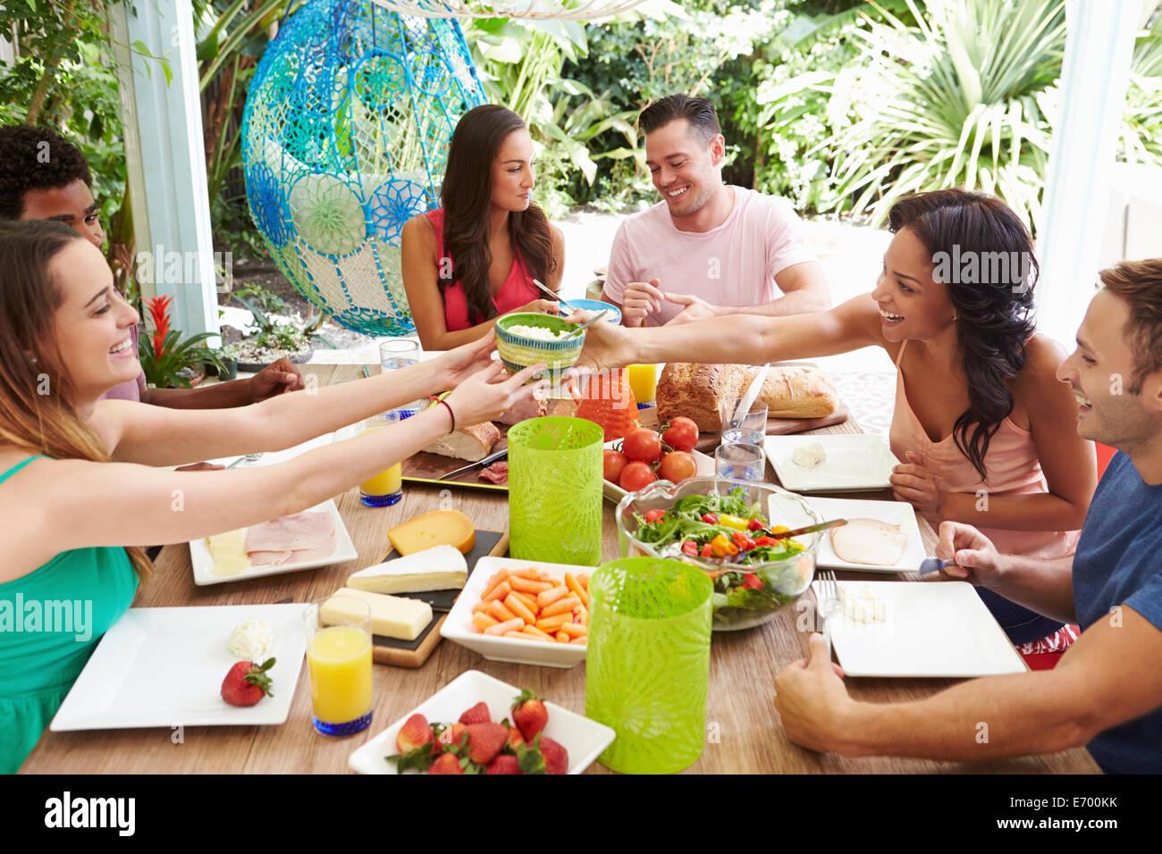 Gruppo di amici gustando pasti all'aperto a casa Immagini Stock