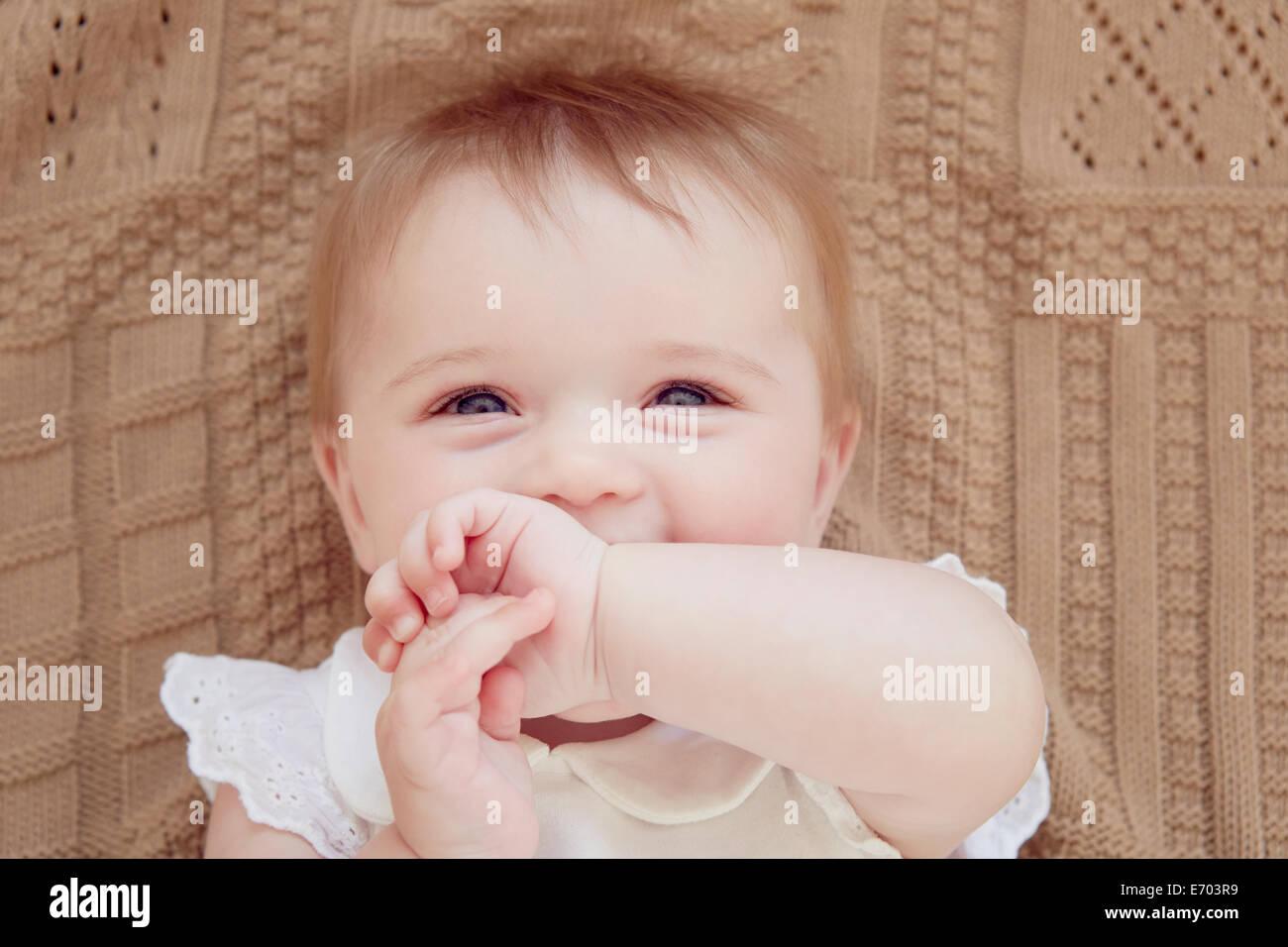 Close up ritratto di sorridente bambina giacente su una coperta Foto Stock