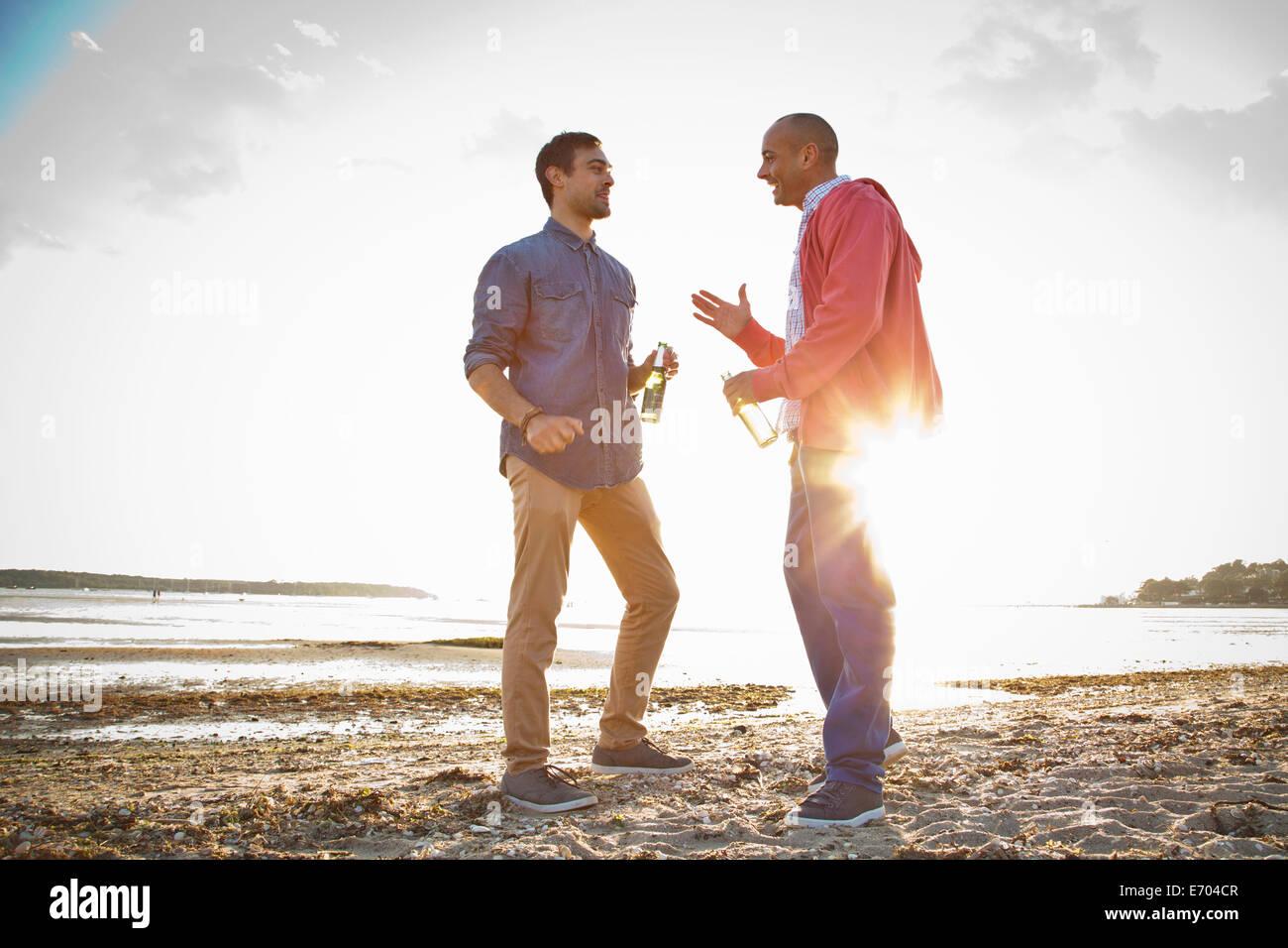Gli uomini di bere birra e conversare sulla spiaggia Immagini Stock