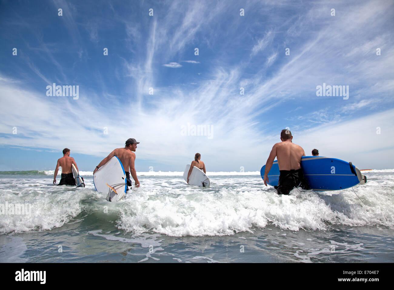 Gruppo di maschio e femmina surfer amici wading in mare con tavole da surf Immagini Stock