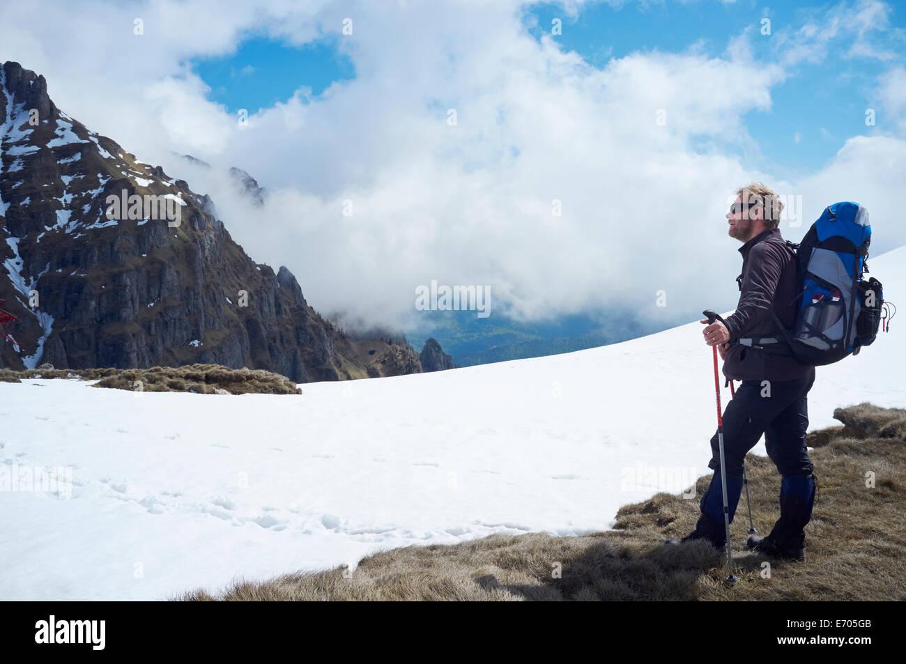 Uomo maturo in piedi nella neve, montagne di Bucegi, Transilvania, Romania Immagini Stock
