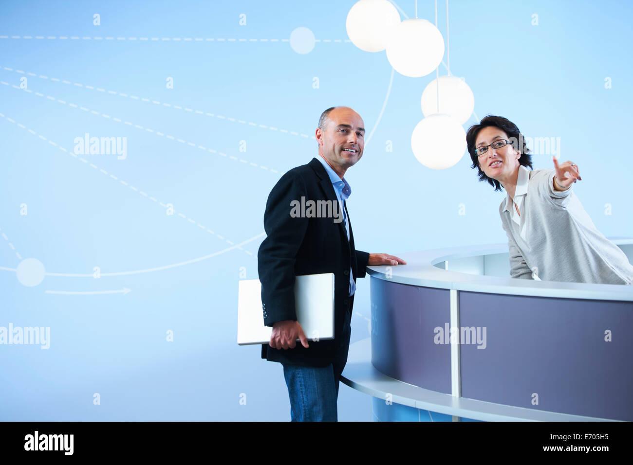 Adulto Uomo chiedendo receptionist per le direzioni Immagini Stock