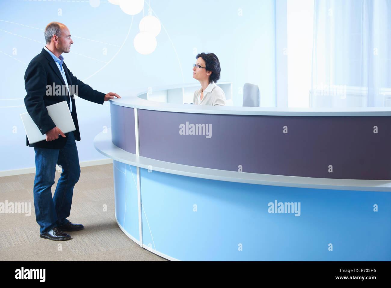 Adulto Uomo parlando a receptionist Immagini Stock
