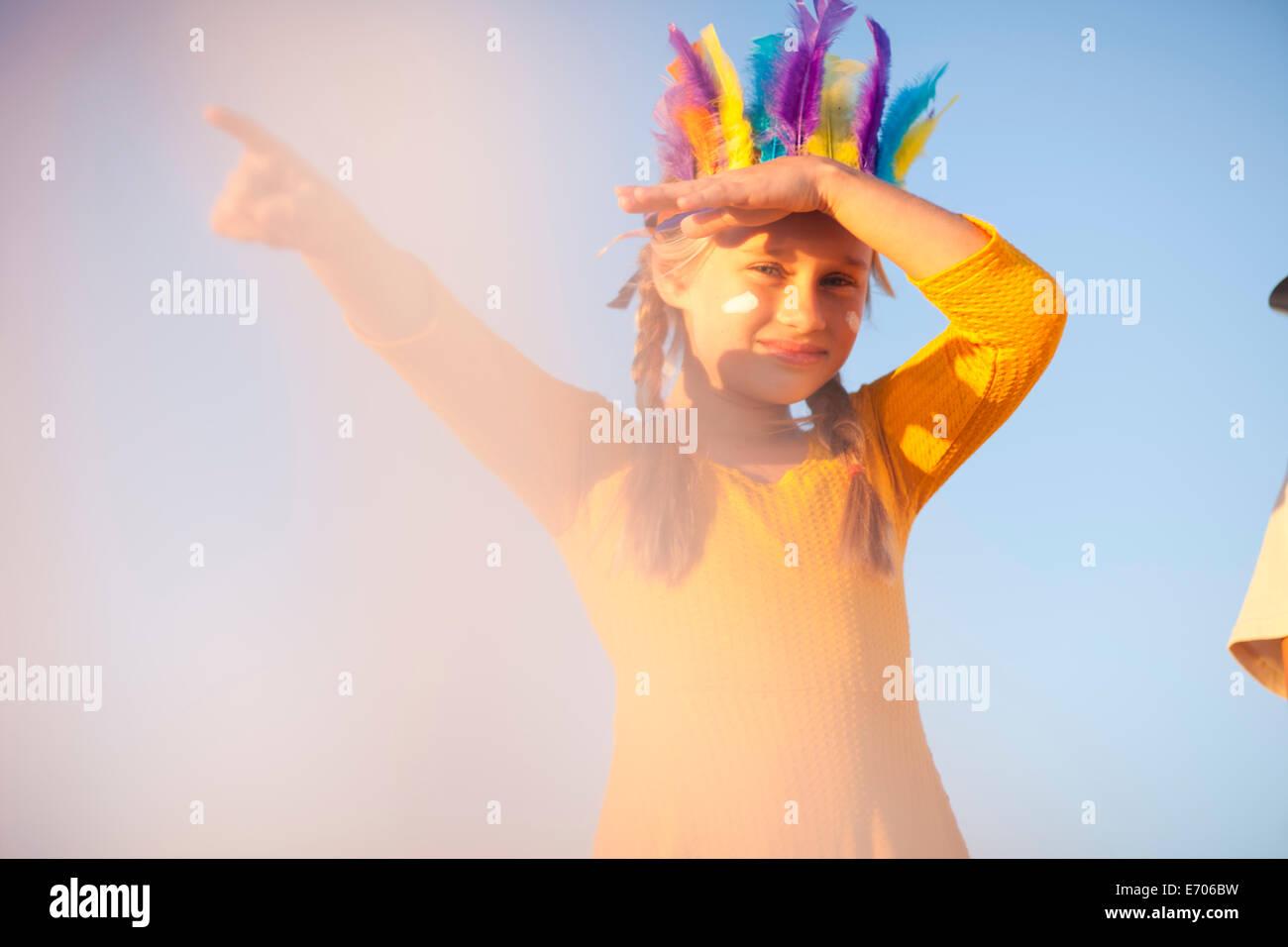 Ragazza vestita come native american in piuma copricapo con mano gli occhi di ombreggiatura e puntamento Immagini Stock