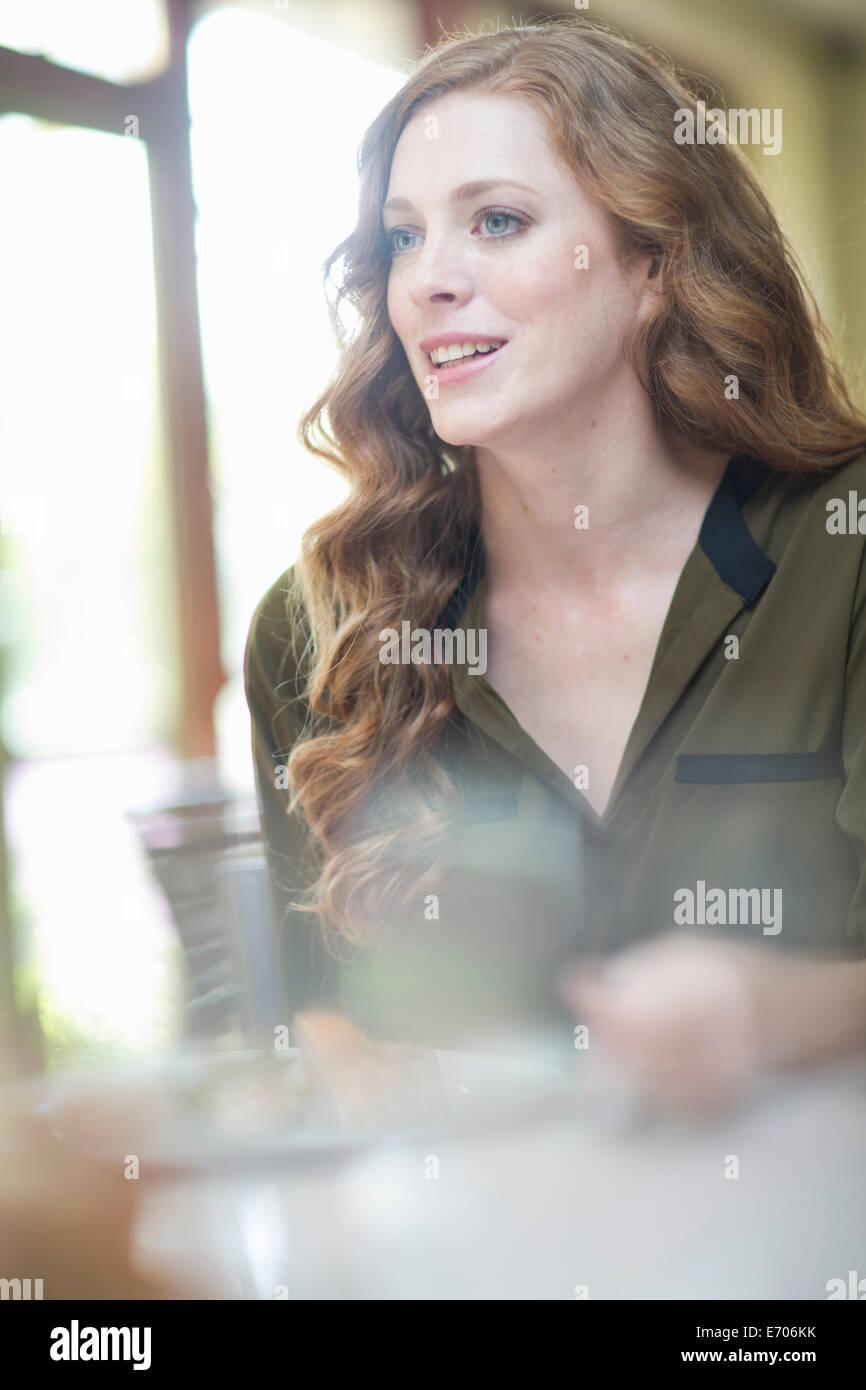 Attraente giovane donna seduta al ristorante tabella Immagini Stock