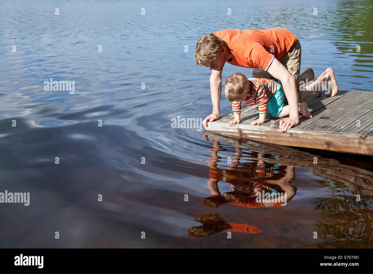 Padre e figlio guardando in giù nel lago dal molo, Somerniemi, Finlandia Immagini Stock