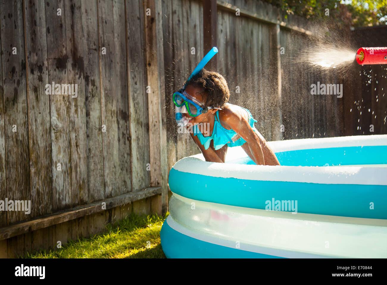 La ragazza di scuba mask getting spruzzato con pistola ad acqua in giardino piscina per bambini Immagini Stock