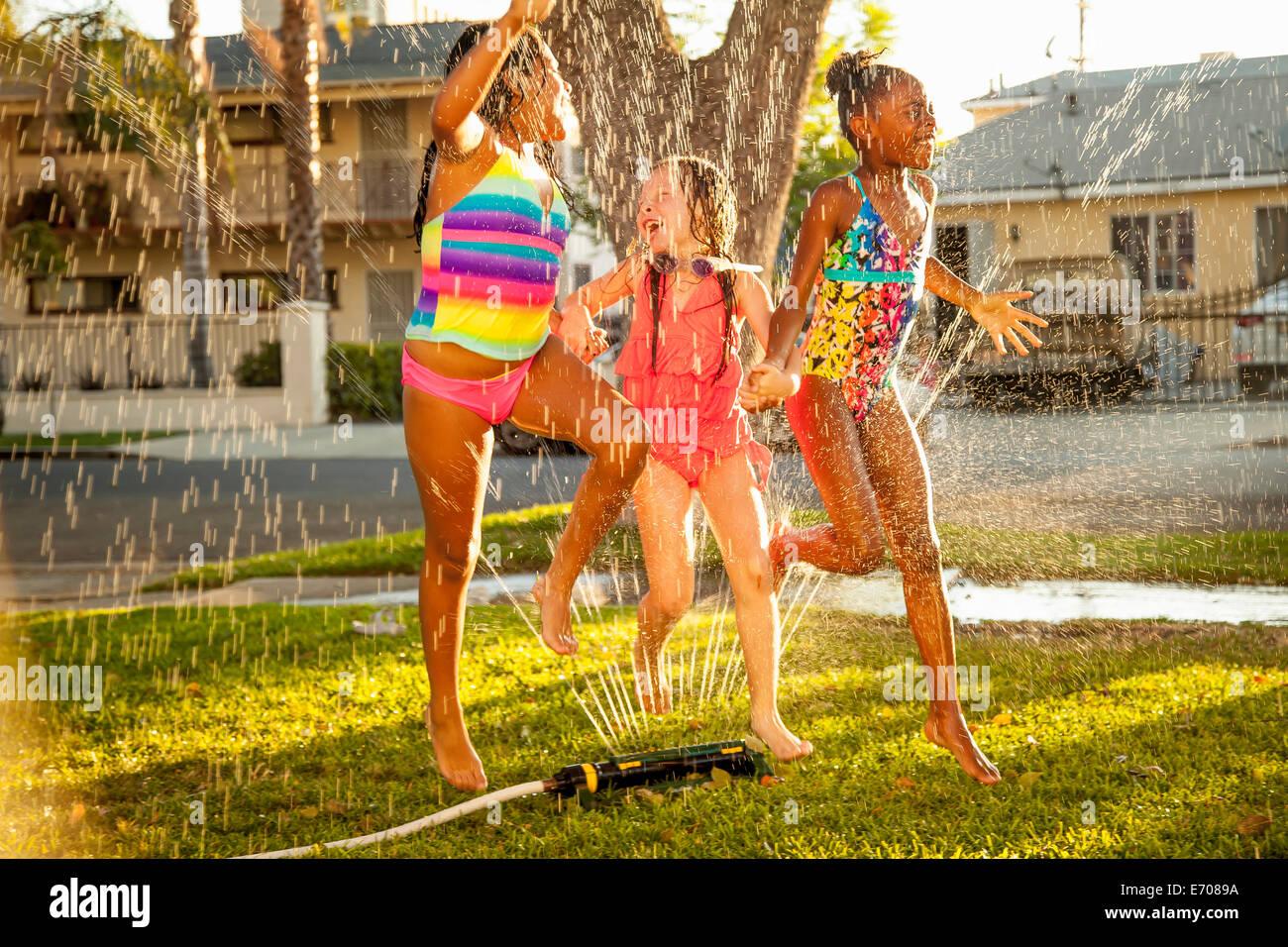 Le tre ragazze correre e saltare in giardino irroratore Foto Stock