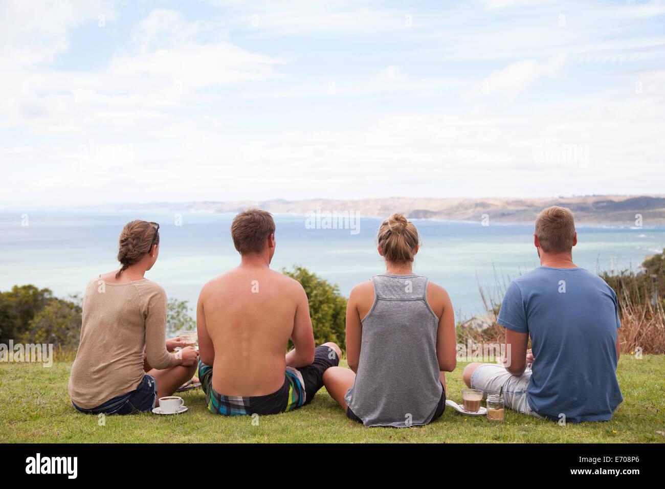 Vista posteriore di quattro amici seduti alla ricerca di distanza al mare Immagini Stock