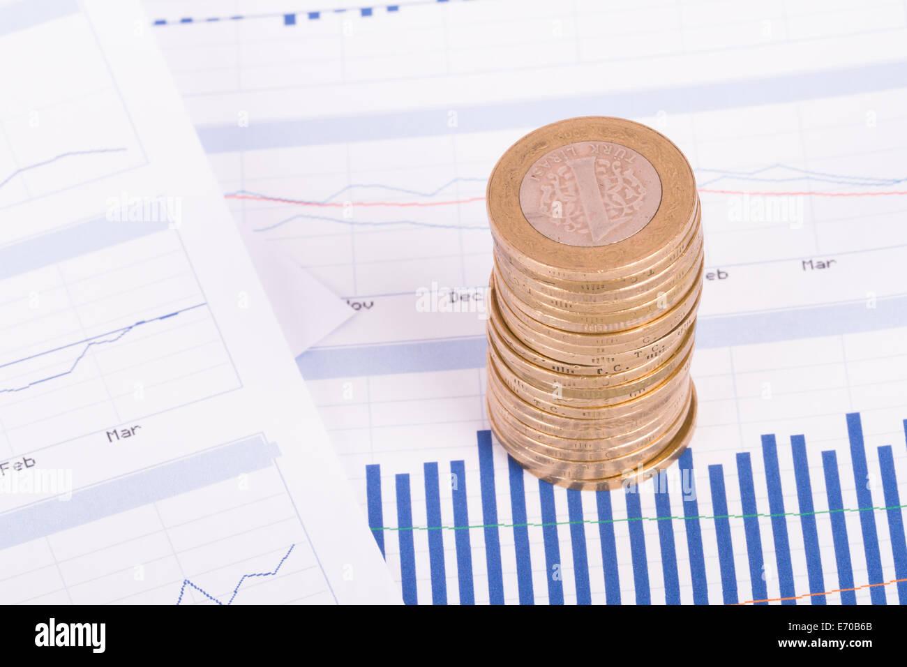 Monete su grafico i grafici e le analisi di dati finanziari. Immagini Stock