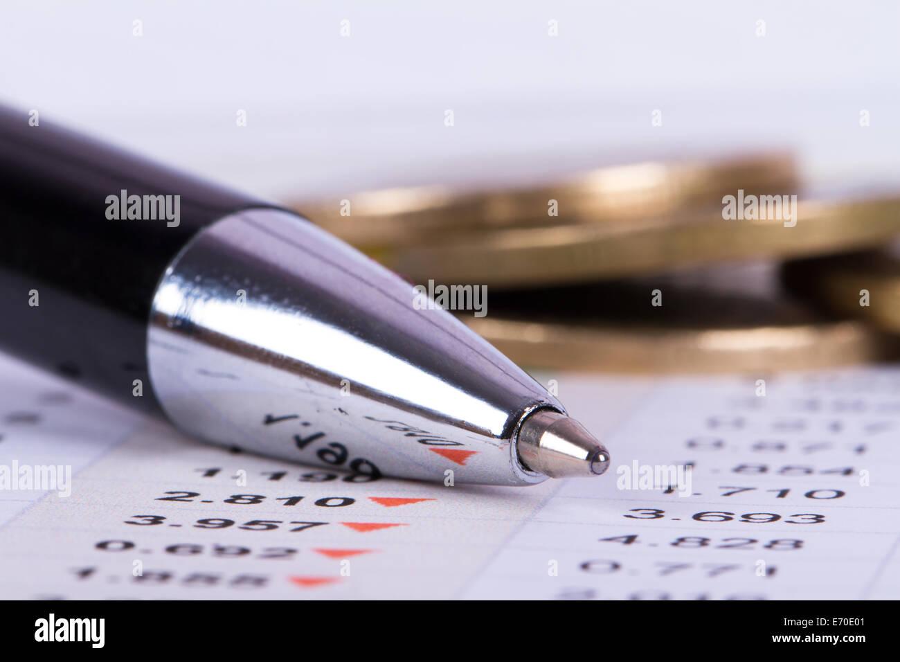 Vista ravvicinata della penna su le analisi di dati finanziari e delle monete metalliche in euro alle spalle. Immagini Stock
