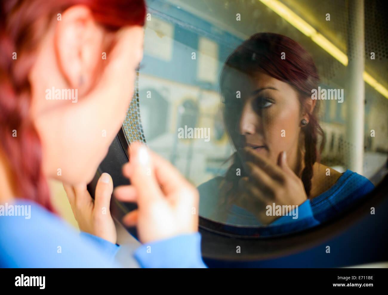 Giovane donna in lavanderia, guardando alla riflessione nella macchina di lavaggio Immagini Stock