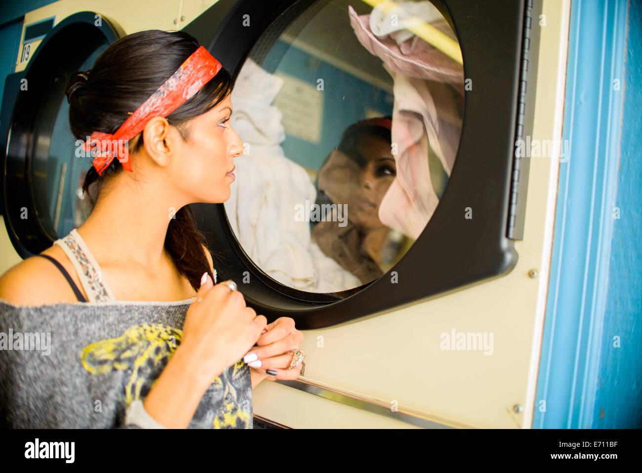 Giovane donna in lavanderia a gettoni, guardando il lavaggio in macchina Immagini Stock