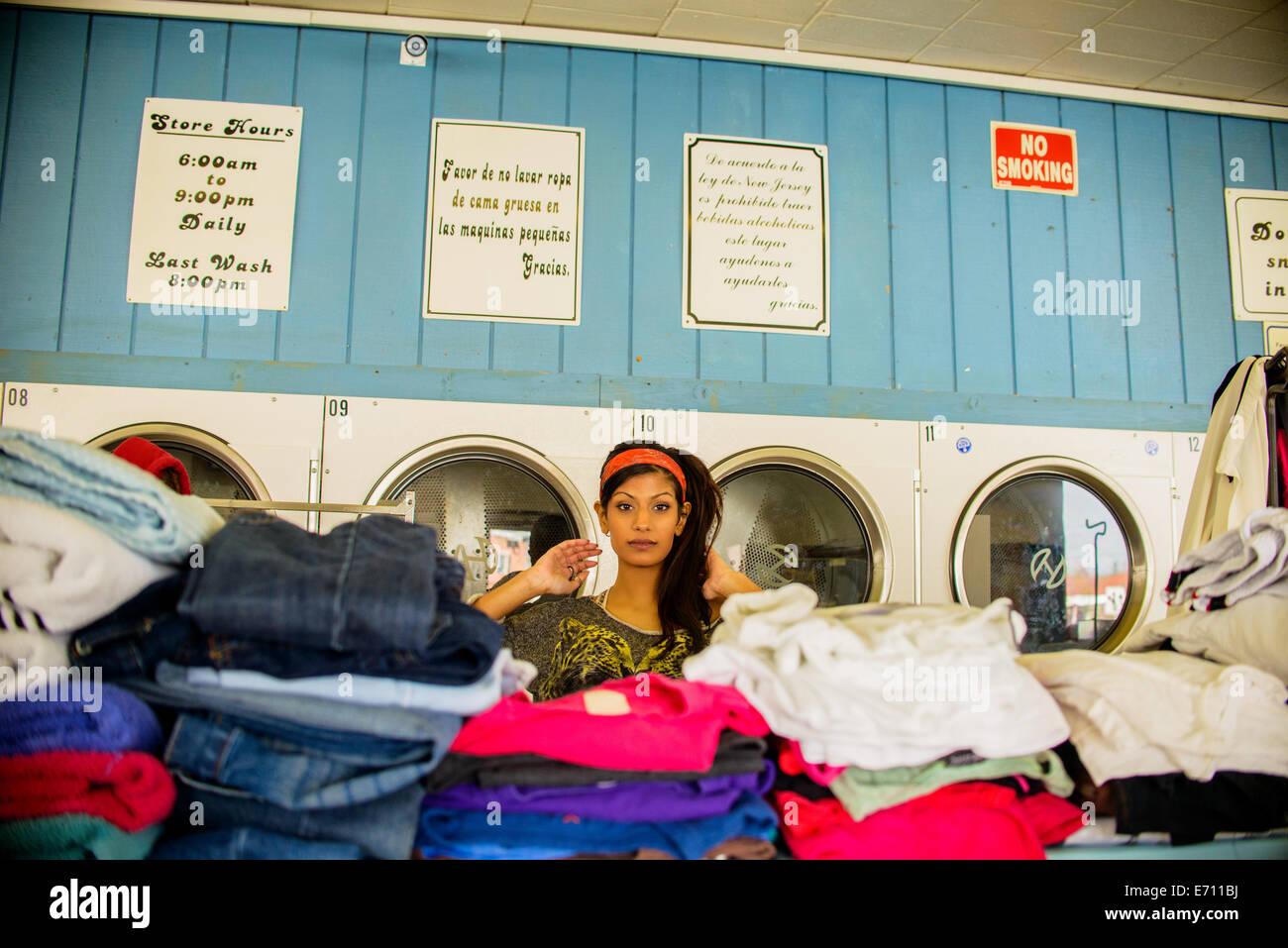Giovane donna in lavanderia a gettoni, in piedi dietro pile di servizio lavanderia Immagini Stock